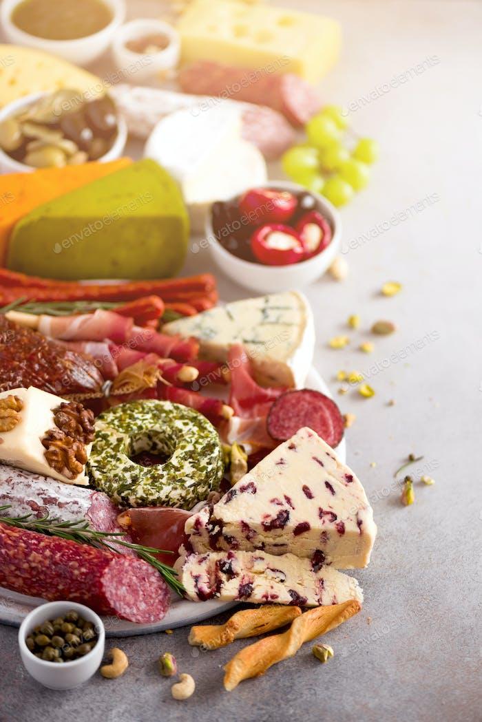 Panel cortar con salami, carne ahumada en frío, jamón, jamón, quesos sobre Fondo gris. Queso y