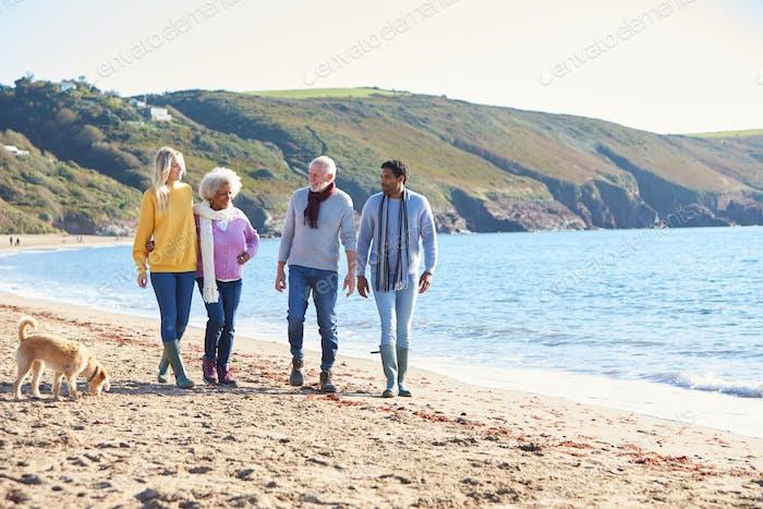 Senior Paar halten Hände zu Fuß entlang Küste mit erwachsenen Nachkommen