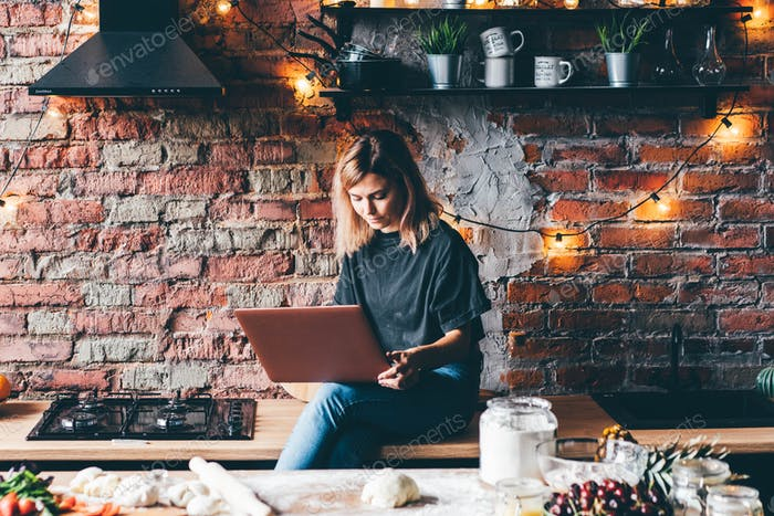 Woman types on laptop, sitting on brown wooden kitchen table at brick wall and smiling.