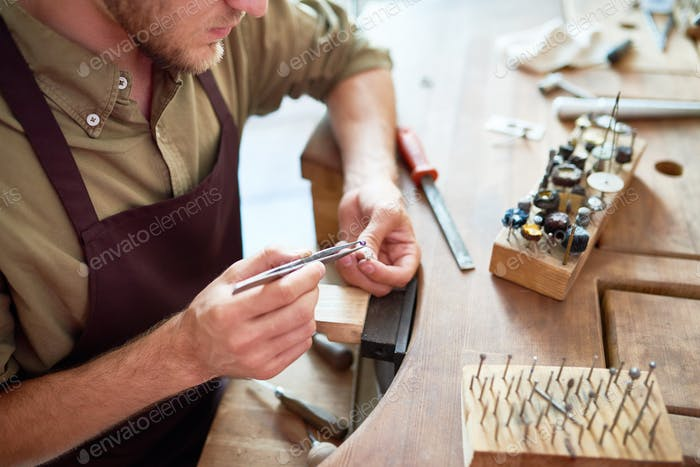 Jeweller Making Silver Ring in Workshop