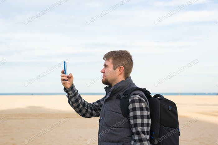 Traveler man taking photos to the beach with smartphone camera on summer travel vacation or hike to