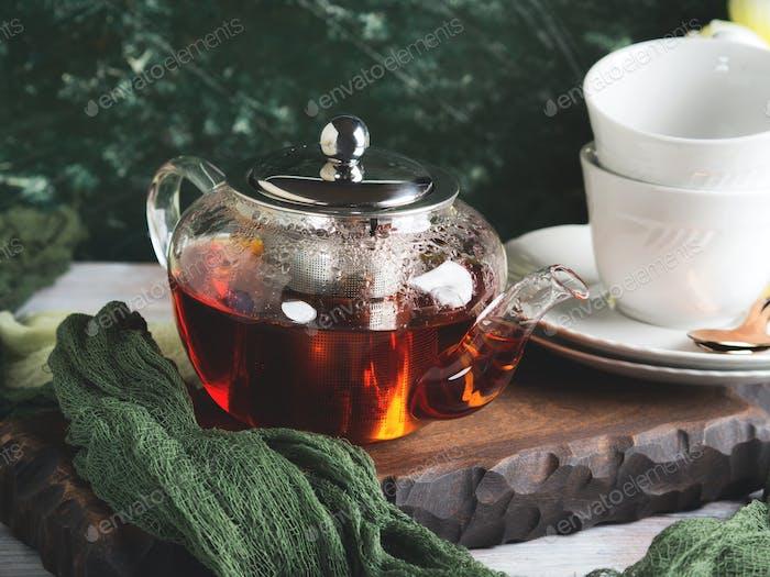 Hot tea in glass tea pot over green background