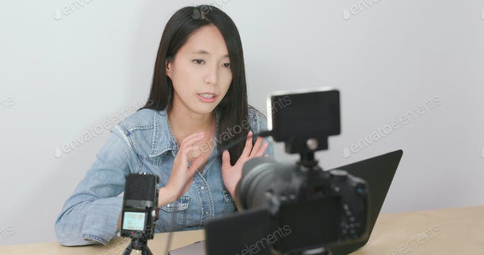 Woman talking in front of the digital camera with her laptop computer for making vlog at home