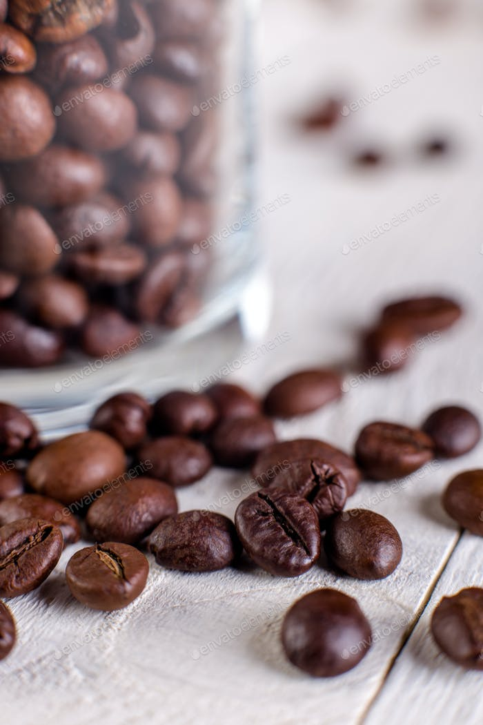 Coffee beans or grain in jar on white wooden background. Macro.