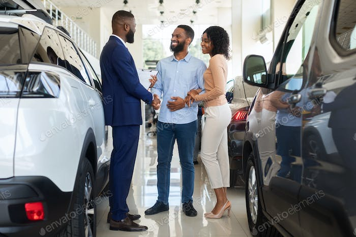 Car Purchase. Happy Customers Couple Handshaking With Manager In Auto Salon
