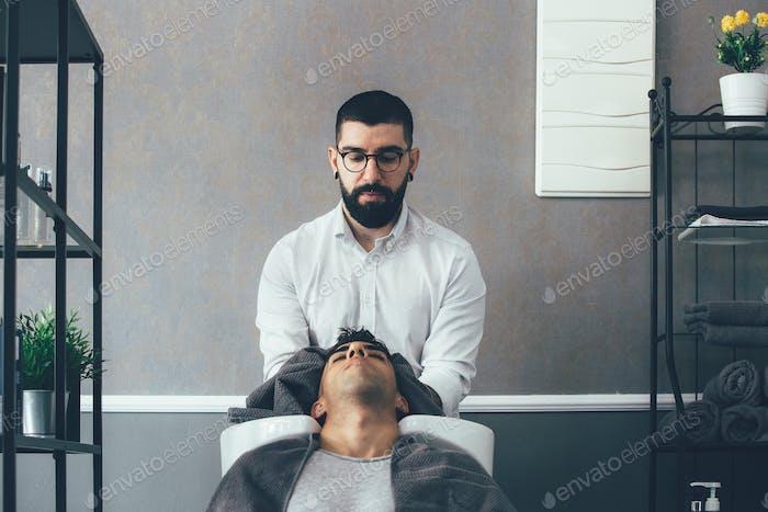 Hairstylist washing head in barbershop