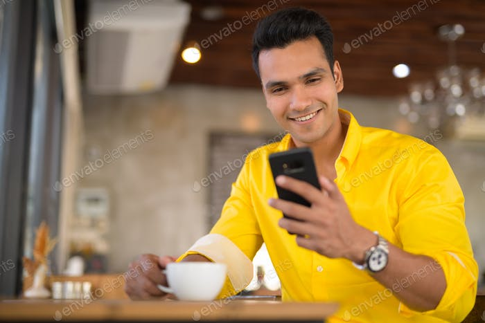 Young happy Indian man using phone and sitting by the window at cafe