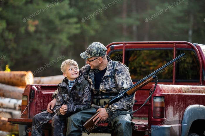 Young hunter boy sit with his father in a truck tailgate