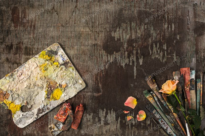 paint brushes and tubes of oil paints on wooden background