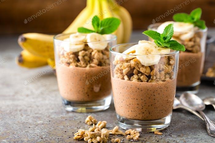 Layered chocolate chia pudding parfait with banana, granola and yogurt, dessert
