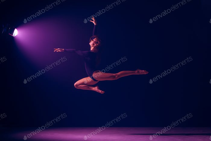 Young female ballet dancer on neon lights studio background.