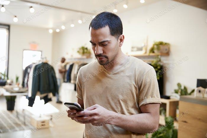 Junge hispanische Mann mit Smartphone in einem Bekleidungsgeschäft