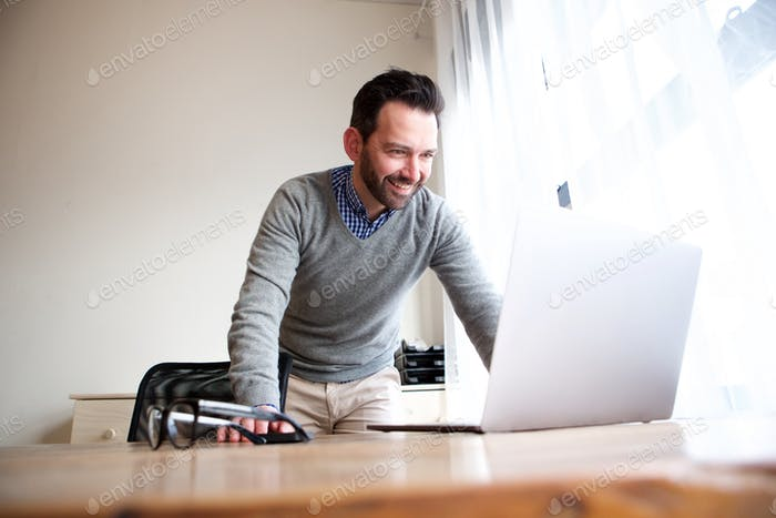 middle age man looking at laptop computer