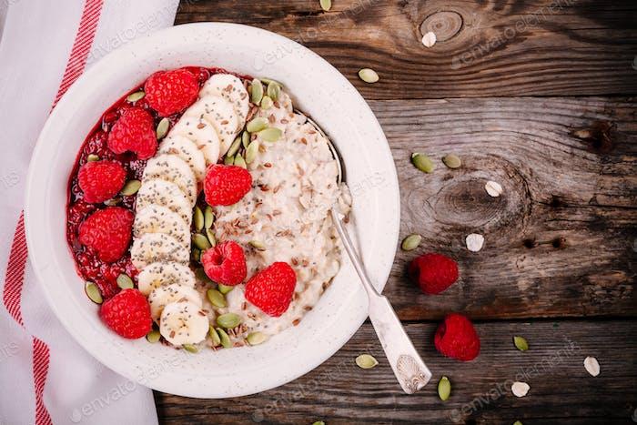 Healthy breakfast: porridge with fresh raspberries, banana, flax seeds and pumpkin seeds