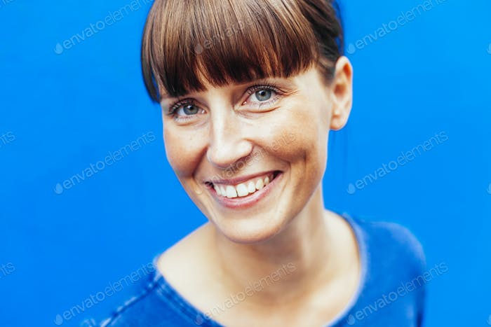 Close-up portrait of happy woman against blue background