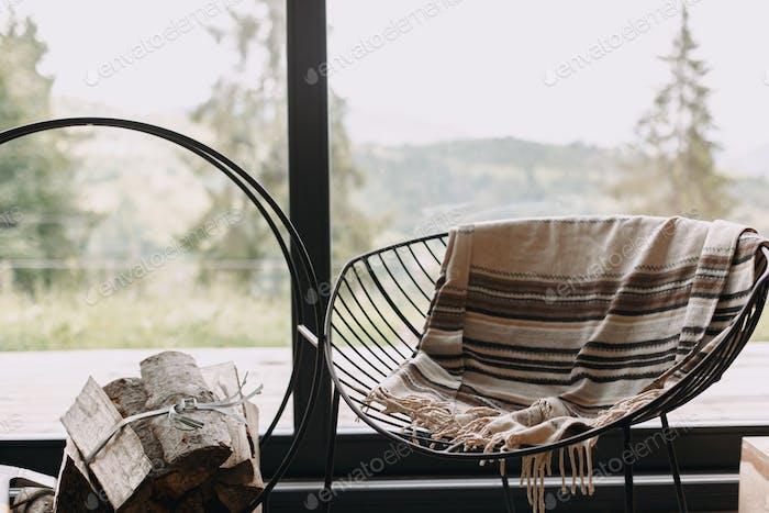 Современный стул с уютным одеялом и дровами на металлической подставке у окна с видом на горы в каюте