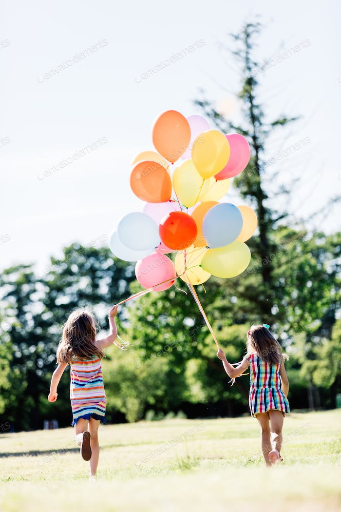Two little girls holding a bunch of balloons together.