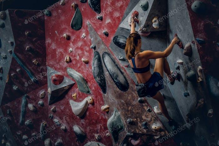 Freie Klettererin weibliche Bouldern drinnen.