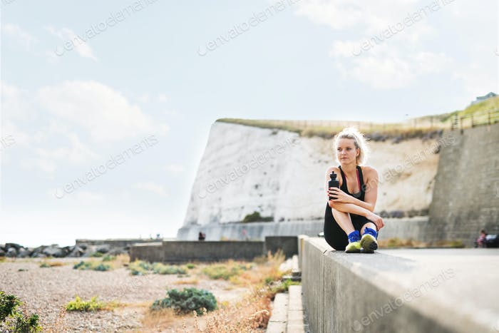 Young sporty woman runner with water bottle sitting on the beach outside.