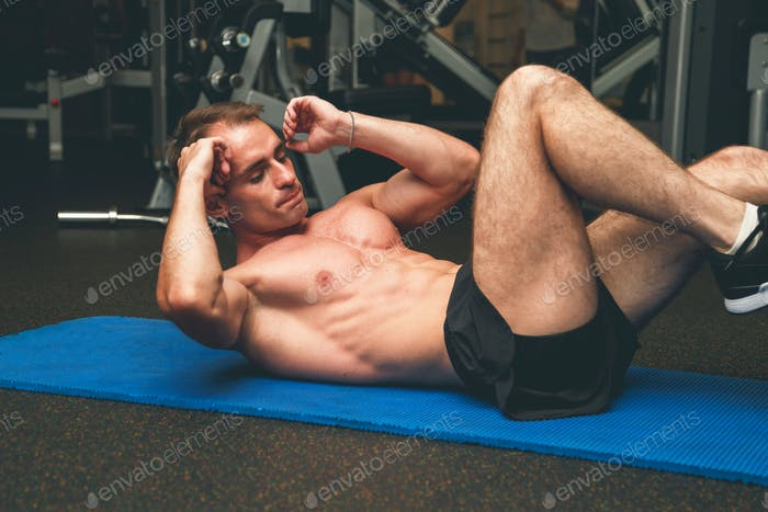 Muscular man on floor working out on abdominal muscles.