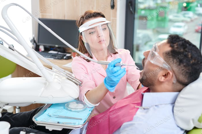 Female Dentist Working with Patient