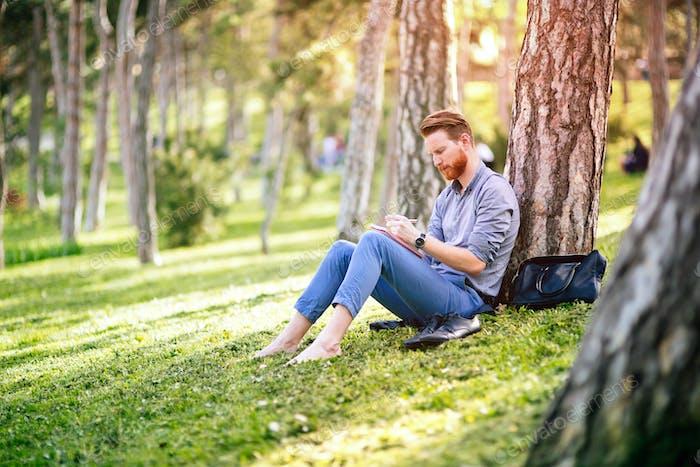 Handsome businessman using tablet pc in park