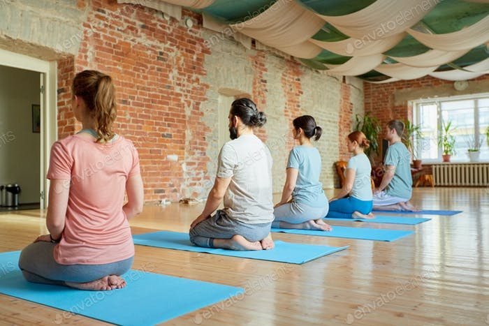 group of people doing yoga kneeling pose at studio