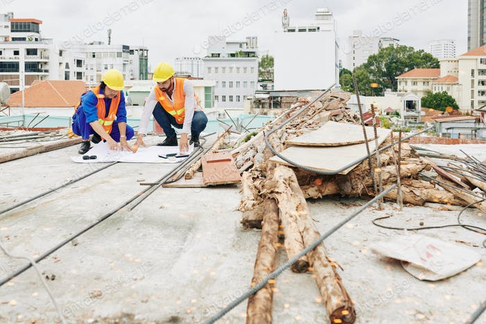 Construction workers checking blueprint