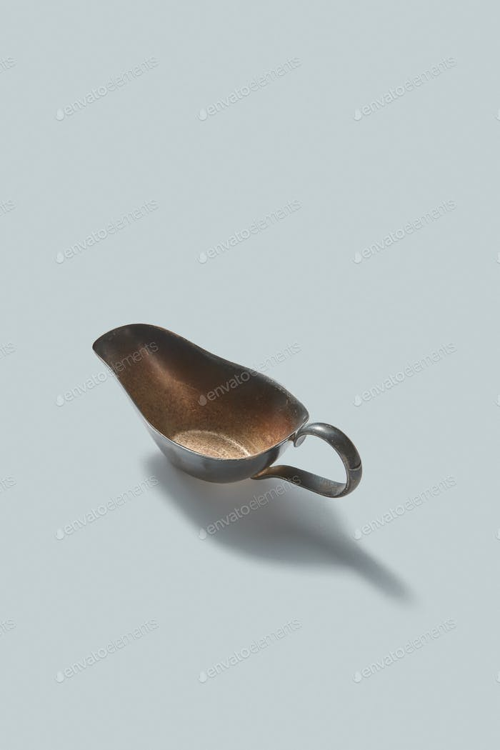 Vintage retro steel empty gravy boat on a white background with shadows, place for text