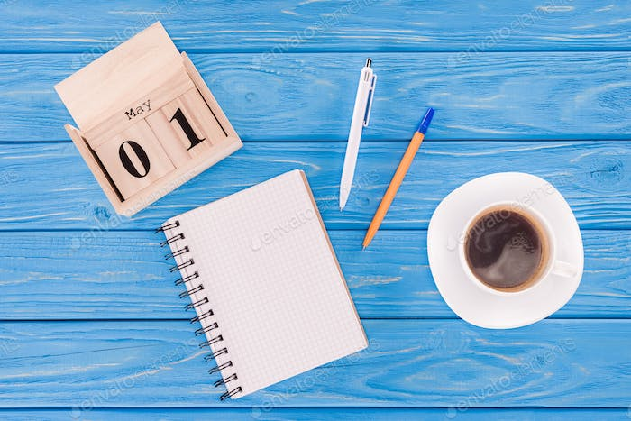 top view of wooden calendar with date of 1st may, coffee cup, empty textbook and pens, international