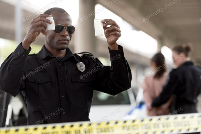 young african american policeman holding drugs in plastic zipper and pills jar