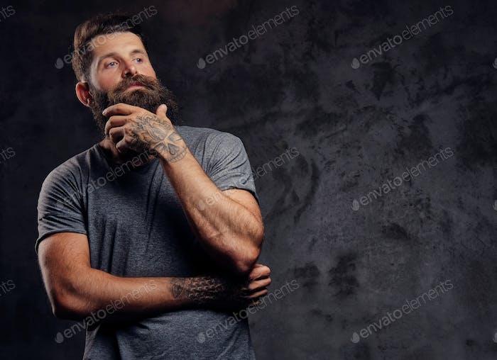 Porträt eines Hipsters mit vollem Bart und stilvollem Haarschnitt, gekleidet in einem grauen T-Shirt in einem Studio