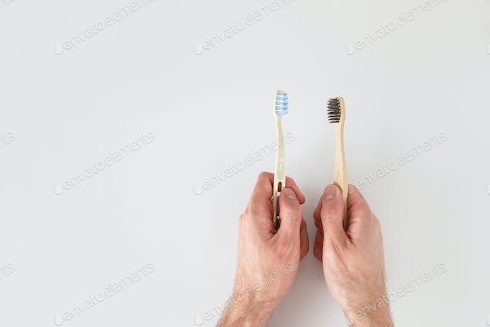 Choose eco material. Hands with two toothbrushes on white background.