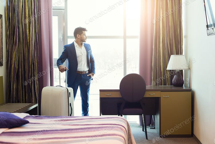 Young businessman with luggage in hotel room