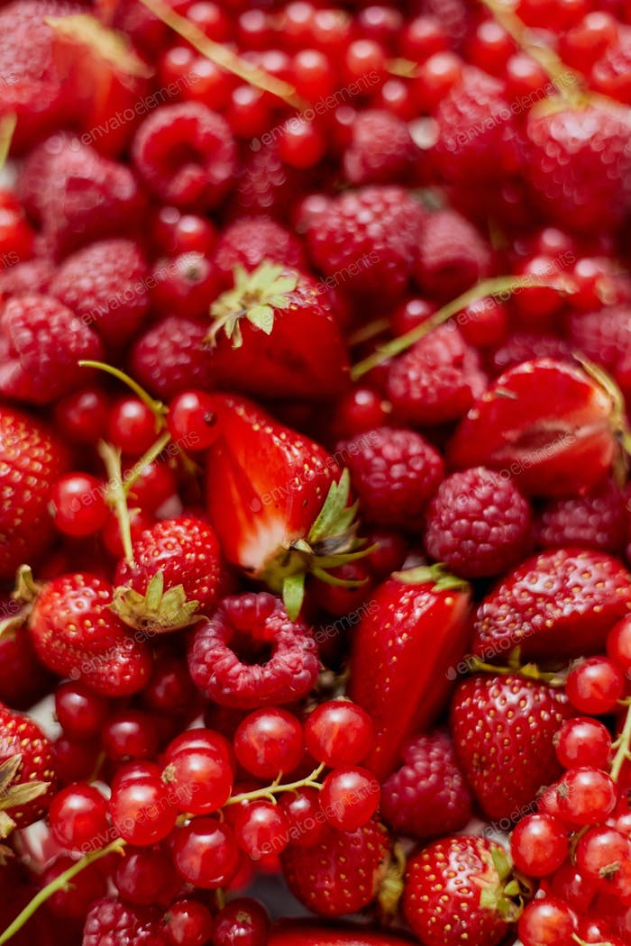 Fresh summer red fruit background composition. Strawberries, red currants, raspberries