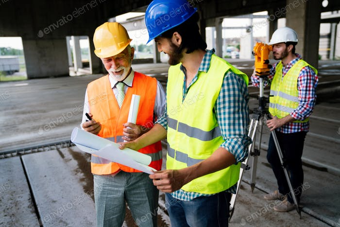 Two satisfied engineers talking at building site with construction structure in background