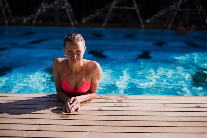 Sexy body of beautiful woman. Girl relaxing in a pool at summer.