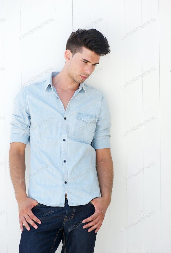 Hombre atractivo de pie al aire libre con las manos en el bolsillo