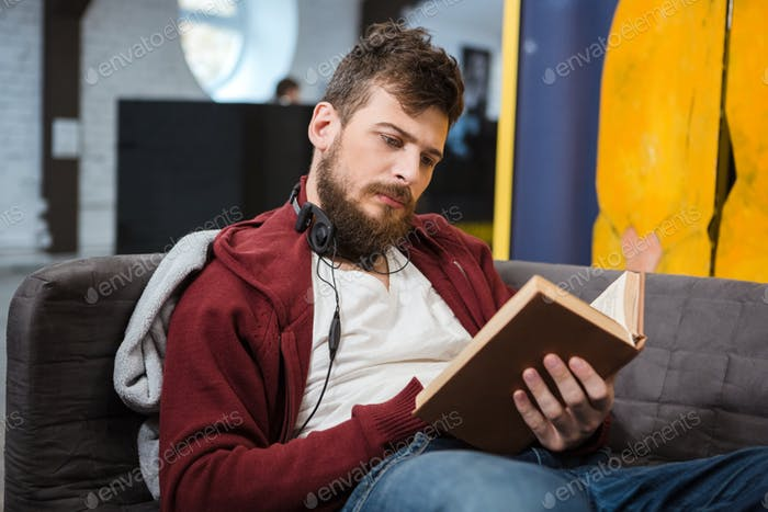 Serious guy sitting on sofa and reading a book
