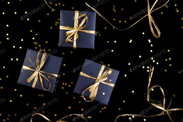 black gift boxes with gold ribbon on shine background flat lay