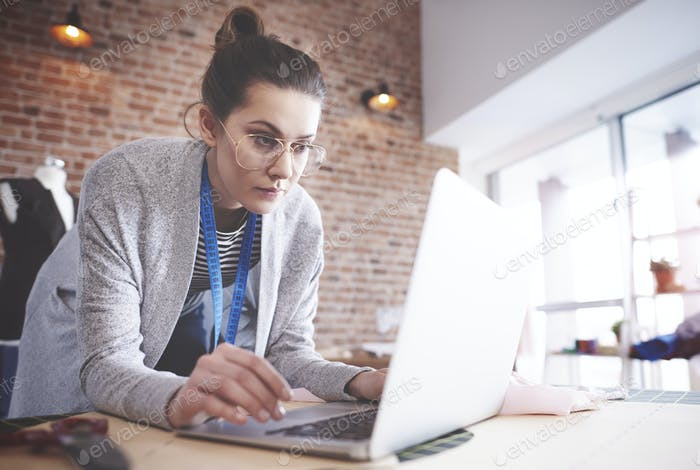 Female dressmaker working on laptop