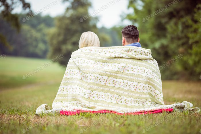 Happy couple sitting under blanket in the countryside