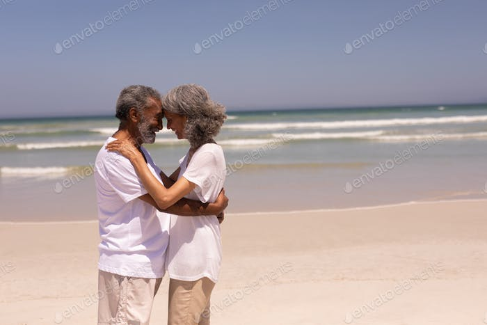 Side view of happy senior couple head to head and embracing each other on beach in the sunshine