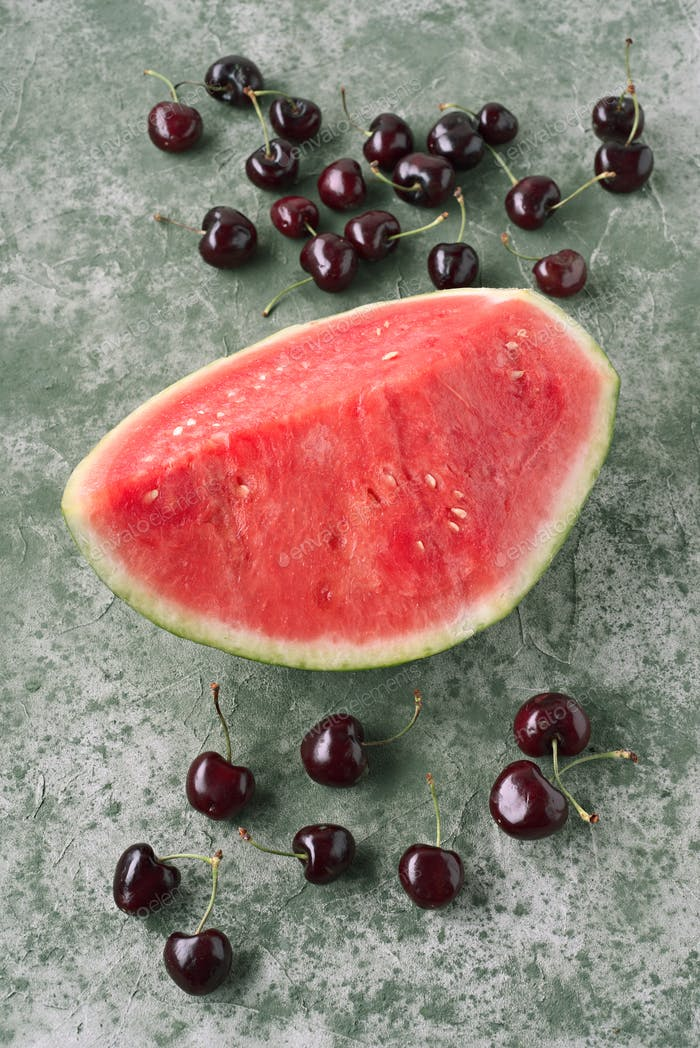 watermelon and cherries on textured green background