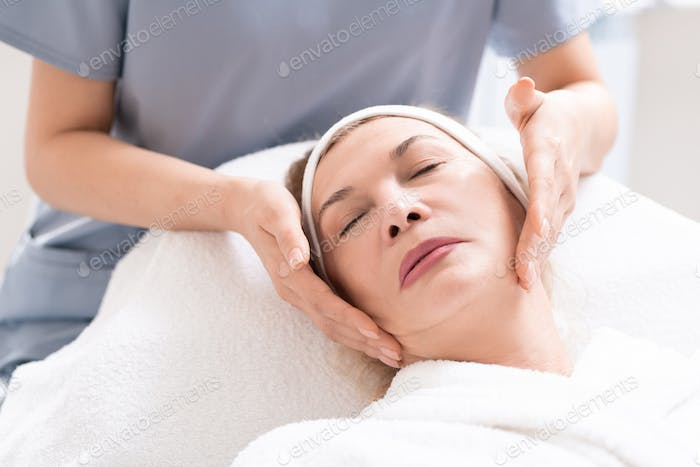 Massaging face of client