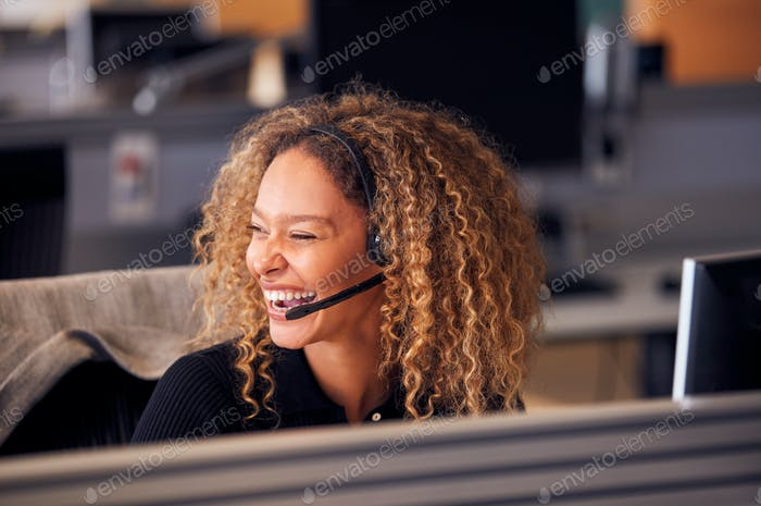 Laughing Businesswoman Wearing Telephone Headset Talking To Caller In Customer Services Department