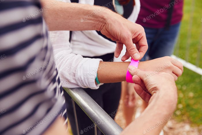 Close Up Of Friends At Entrance To Music Festival Putting On Security Wristbands