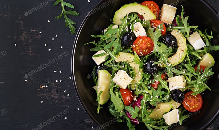 Green salad with sliced avocado, cherry tomatoes, black olives and cheese.
