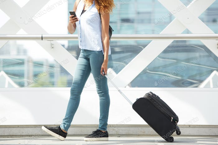 young woman walking with suitcase and mobile phone at station