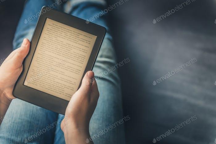 Mädchen liest eBook auf digitalem Tablet-Gerät